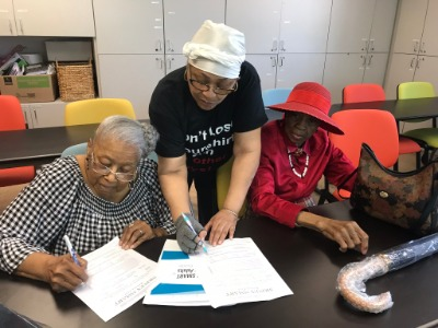 Three elderly ladies completing a form